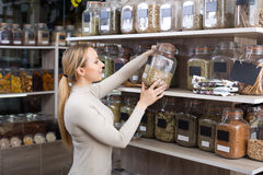 Woman with dried herbs in organic store. Smiling young woman holding jars with dried herbs in organic store stock photography