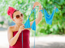 Woman dries blue bikini on clothesline Royalty Free Stock Images