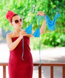 Woman dries blue bikini on clothesline Royalty Free Stock Photography
