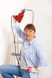 Woman with drill. Beautiful woman working with red drill, wearing protective glasses and gloves, ladder in background Stock Photos