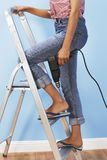 Woman With Drill Climbing Ladder Royalty Free Stock Images