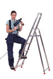 Woman with drill. Stood on step ladder Stock Photo