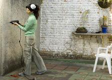 Woman Drilling into Wall - Horizontal Stock Images