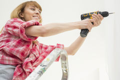 Woman drilling wall in new house Stock Photos