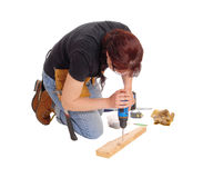 Woman drilling in wood. A middle age woman kneeling on the floor and working with some tools drilling in wood, isolated for white background stock photography