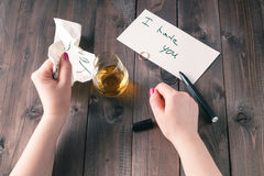 Woman drink alcohol and write message Stock Photo