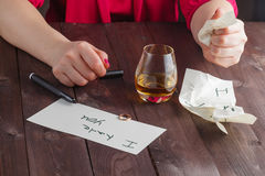 Woman drink alcohol and write message Stock Images