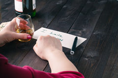 Woman drink alcohol and write message Royalty Free Stock Image