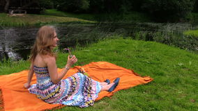 Woman drink cider champagne alcohol sitting on plaid near river. Healthy nutrition in nature. Shot on Canon XA25. Full HD 1080p. Progressive scan 25fps. Tripod stock video footage