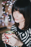 Woman drink cocoa with marshmallows in front of xmas lights Royalty Free Stock Photography