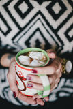 Woman drink cocoa with marshmallows in front of xmas lights Stock Photography