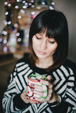 Woman drink cocoa with marshmallows in front of xmas lights Stock Photos