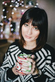 Woman drink cocoa with marshmallows in front of xmas lights Royalty Free Stock Images