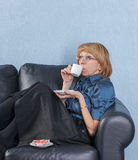 Woman drink coffee on couch Royalty Free Stock Images
