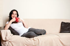 Woman with drink on couch Stock Images