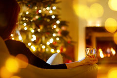 Woman with a drink by a fireplace on Christmas