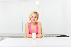 Woman drink glass of milk in her kitchen Stock Image