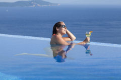 Woman with drink in infinity pool. Woman in swimsuit with sunglasses holding a tropical drink in infinity pool overlooking blue waters Royalty Free Stock Images