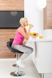 Woman drink orange juice glass in her kitchen Stock Images
