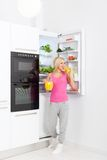 Woman drink orange juice hold glass refrigerator Royalty Free Stock Photos