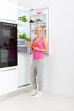 Woman drink orange juice hold glass refrigerator Royalty Free Stock Photos