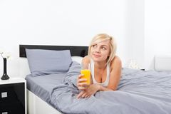 Woman drink orange juice, lying on bed Royalty Free Stock Photo