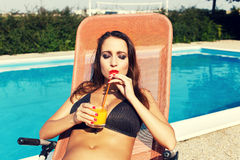 Woman drink orange juice with straw at swimming pool Stock Photography