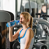 Woman drink water at fitness machine Royalty Free Stock Image