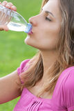 Woman drink water grass Stock Photo