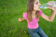 Woman drink water grass Stock Image