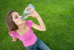 Woman drink water grass Royalty Free Stock Image