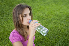 Woman drink water grass Royalty Free Stock Photography