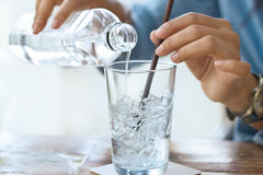 Woman drink water with ice in glass on a table in restaurant Royalty Free Stock Photo