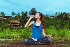 Woman drink water in lotus pose.