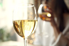 Woman drink white wine with friend in restaurant. Two glasses Royalty Free Stock Images