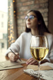 Woman drink white wine near window in restaurant.  Stock Photo