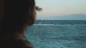 Woman drink wine and look how people Kite surfing in beautiful clear water in Dahab Egypt. Exploring the blue sea with
