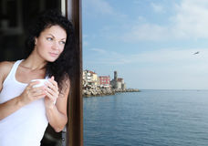 Woman Drinking. A beautiful woman with a cup of coffee  near the window Stock Photography