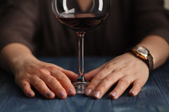 Woman drinking alcohol on dark background. Focus on wine glass stock images