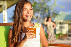 Woman drinking alcohol Mai Tai drink on Hawaii. At beach club at sunset. Beautiful girl enjoying alcoholic beverage cocktail outside. Smiling happy mixed race Royalty Free Stock Photography
