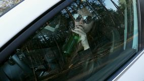 Woman drinking alcohol sitting behind the wheel of a car, traffic offense. Woman drinking alcohol while sitting behind the wheel of a car, traffic offense drunk stock video footage
