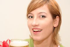 Woman drinking a beer. Smiling woman drinking a big glass beer Royalty Free Stock Image