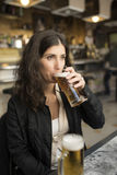 Woman drinking beer in bar Royalty Free Stock Photography