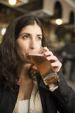 Woman drinking beer in bar Stock Images
