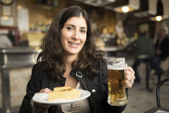 Woman drinking beer in bar. Happy woman drinking beer in bar with ambient and natural lightning Royalty Free Stock Photo