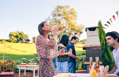Woman drinking beer in a barbecue with friends Royalty Free Stock Photography
