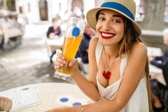 Woman drinking a beer in Bavaria. Young female tourist sitting with beer outdoors at the pub in Munich, Germany. Woman drinking a beer in Bavaria Royalty Free Stock Image