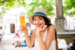 Woman drinking a beer in Bavaria. Young female tourist sitting with beer outdoors at the pub in Munich, Germany. Woman drinking a beer in Bavaria Stock Images