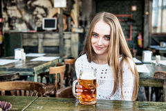 Woman drinking beer at the cafe Stock Photos