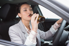 Woman drinking beer while driving Stock Photography